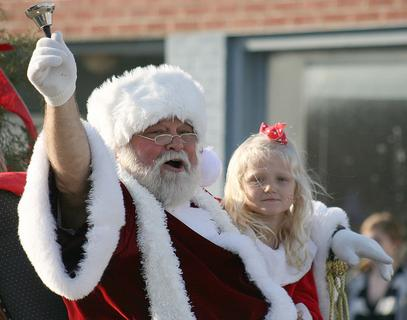 Santa Claus and his friend, Vanessa Van Why, 5, wave to people