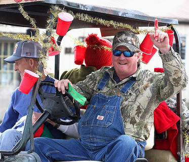 Tony Purdom has fun with the crowd as he drives his Kubota decorated with red solo cups during the parade.