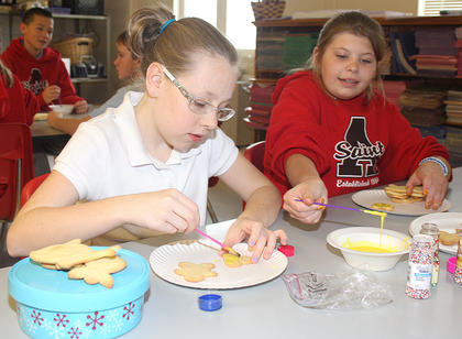 Ellie Buckman and Sarah Barnes share the yellow icing as they decorate their cookies.