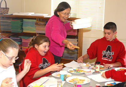 Susan Spicer hands out cookies to a table full of students. Pictured, from left, are Ellie Buckman, Sara Barnes (who looks extremely excited with her cookie selections) and Dawson McCarty.