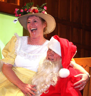 Charlotte Brady Mattingly, playing the part of Minnie Pearl, sits on Santas lap and tells him what she wants for Christmas.