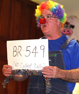 "State Rep. Terry Mills plays Junior Samples, a used car salesman, during the ""Samples Sales"" skit. Junior tries to palm off a major clunker and then holds up a sign to remind viewers that his phone number is ""BR-549."""
