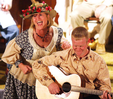 Members of the St. Joe community re-created their own HEE HAW show Sunday evening and entertained a packed house with skits, musical entertainment and lots of corny jokes. Hee Haw will be performed once again on Jan. 1, 2012 at the former St. Joe Church. Pictured is Minnie Pearl (Charlotte Mattingly) entertaining the crowd while Nathan Yaste plays the guitar.