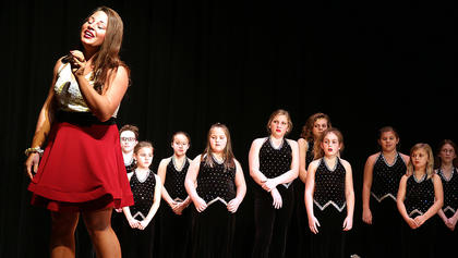 Aubrey Skutt-Davis sings with the Centre Square Youth Choir watching in the background.