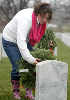 Despite rain and cold temperatures, Marion County residents, veterans, and Patriot Riders gathered at the Lebanon National Cemetery to honor the living and remember the fallen by placing wreaths at their final resting spots. On Dec. 14, people all over the country did exactly the same thing. Like many in attendance, Melissa Hoisington braves the rain as she places a wreath on a soldier's resting place.