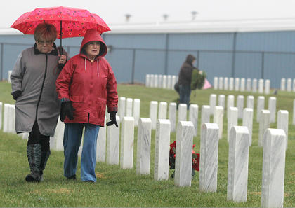Marie Stoltzfus and Winifred Pickerill Crawford walk by a line of tombstones after placing wreaths.