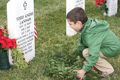 The Wreaths Across America event was held Saturday at the Lebanon National Cemetery. Approximately 447 wreaths were placed on headstones to remember all soldiers, sailors, airmen and marines who served. Specially designated wreaths for the Army, Marines, Navy, Air Force, Coast Guard, Merchant Marine and POW/MIA were placed on memorials during the ceremony. Lebanon Middle School raised more than $1,000 for the event. See more photos on the Enterprise web site. Pictured is Aiden Phillips, 6, lays a wreath near his grandfather&#039;s headstone at Lebanon National Cemetery. His grandfather, Todd Lanham, passed away on Sept. 3, 2011.