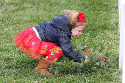 Molly Mattingly carefully places a wreath near a headstone at the cemetery. 