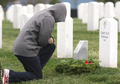 A volunteer takes a moment to pay his respects while laying a wreath at a headstone.