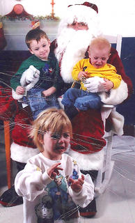Pictured are the May children with Santa Claus. Isiah May smiles on Santa's lap, while Michaela runs from Santa to Papaw and Mason cries. Santa was actually their uncle, Dennis May.