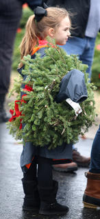 Mary Beth Masterson holds one of the wreaths and waits to place it on a headstone at the Lebanon National Cemetery.