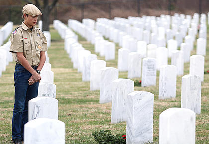 Andrew Beltz, a Boy Scout in Campbellsville Troop 616, volunteers during the Wreaths Across America Day ceremony held at the Lebanon National Cemetery Saturday.