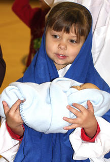Mya Hill plays the part of the blessed Virgin Mary holding baby Jesus.