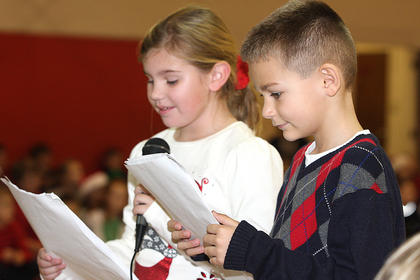 Zoey Blair and Bryce Thompson read a special Christmas story while their classmates act it out behind them.
