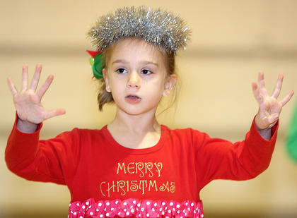 Anna Ray Wheatley sings during the performance at St. Augustine Grade School for its Christmas program Friday morning.
