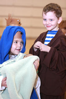 Preschoolers, kindergarteners and first-graders at St. Augustine performed Christmas songs and acted out a Christmas story for their family and friends on Dec. 18. Pictured are Madison Mattingly and Hayden Lanham portrayed Mary and Joseph with the baby Jesus.