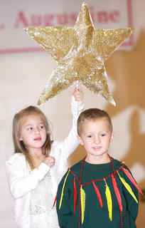 Brooklyn Mattingly holds a star in place over Drew Morgan, who was playing a fir tree who dreamed of being a Christmas tree.