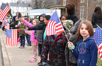 "Laney Summers, a second grader at Lebanon Elementary School, joins her classmates as the entire student body and staff at LES lined Main Street Friday, Dec. 18, holding American flags to pay their respects to Horatio ""Bud"" Olive, 79, of Louisville who died Dec. 8. He was buried in the Lebanon National Cemetery."