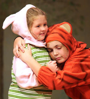 Tigger, played by Izzy Lyers, gives Piglet, played by Sophie Ballard, a big hug.