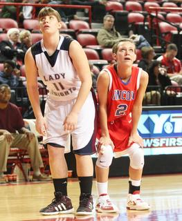 Senior Coco May prepares to block out a Lincoln County player while a teammate shoots a free throw.
