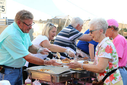 Keith Brock and Ruthie Jackson serve generous helpings of potato salad and barbecue to Brenda Harmon and Peggy Birmingham during Lebanon Main Street's Pigout on Proctor Knott event Thursday evening in Lebanon. The barbecue dinner was catered by Smokey D's BBQ.
