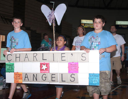 The Charlie&#039;s Angels team walks in the parade of teams. Chas Brubeck, left, Angelina Parrott and Andrew Tungate led the way.