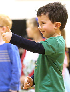 Dylan Leathers gives a thumbs up to the crowd during the preschool's performance.