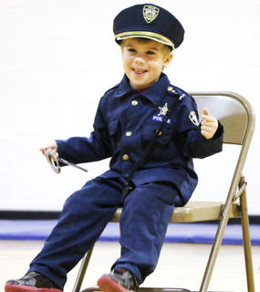 """Alex Mullins cheeses at the crowd as he and his siblings, Jenna and Ethan, perform a routine to """"Jailhouse Rock."""""""