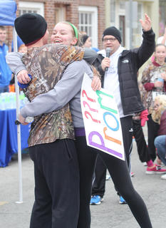 Madelyn Hagan embraces Robbie Spalding after he asked her to prom at the finish line.