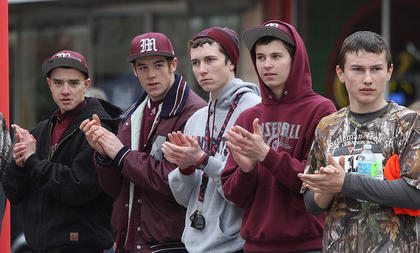A group of Marion County baseball players cheer on runners as they cross the finish line.