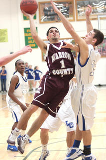 Senior Josh Brockman puts up a shot as he shields a LaRue County defender in the opening round game of the boys 5th Region tournament. The Knights defeated the Hawks 55-53.