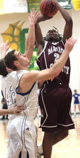 Junior Carlos Litsey puts the ball back in off of a rebound in the opening round game against LaRue County.
