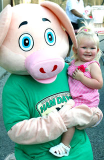 One-year-old Kaitlynn Nalley poses with Piggles at the Pigout on Proctor Knott Thursday evening. Her parents are Crystal and Chuck Nalley.