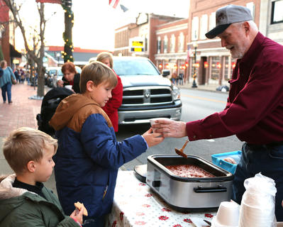 Tommy Glasscock serves Jackson Truitt a bowl of chili as Jackon's brother, Sam, enjoys a cookie. Glasscock won this year's Marion County Chamber of Commerce's Chili Cook Off. That Cute Little Shop won second place.