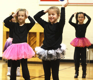 "From left, second graders Gracie Benningfield, Brooklyn Mattingly and Amira Bowman perform the ""Macarena."""