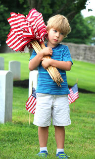 Alex Mullins, 4, of Lebanon helps with gravesite flag decoration at the Lebanon National Cemetery prior to Memorial Day.