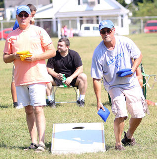 Charles Thompson (left) of Georgetown and Tony Thompson (right) compete in the Cornhole Competition Saturday.