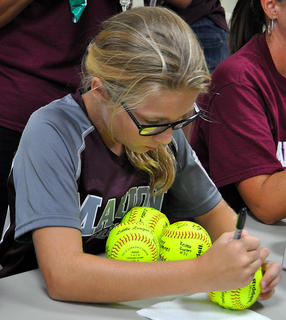 Gracie Benningfield signs autographs of state team championship balls.