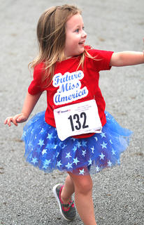 Klaire Garrett waves to her fans as the future Miss America as she nears the finish line.