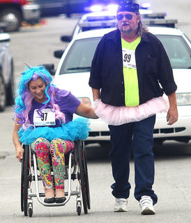 "Terri Rozaieski, left, and Derek Howard, both of Springfield, finish the Back Tutu School Run/Walk hand in hand. Rozaieski won an award for having the most ""spirit and spunk."""