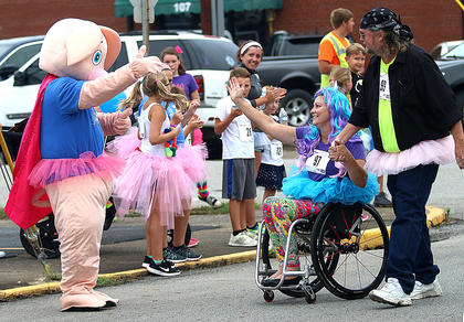 "Terri Rozaieski, left, and Derek Howard, both of Springfield, get some encouragement from Piggles as they near the finish line. Rozaieski won an award for having the most ""spirit and spunk."""