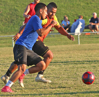 Aldo Perez (in red) puts the pressure on Christian Carmona (in blue) for possession of the ball during the alumni soccer game on Friday.