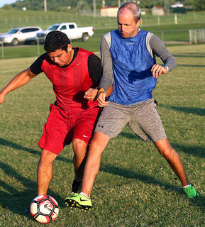 Eddie Ponce, left, and MCHS Girls Soccer Head Coach Daniel Johnson jossle for the ball during the alumni game Friday.