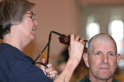 Vicki Childers puts the finishing touches on Joe Paul Mattingly&#039;s head. Mattingly was representing Marion County Farm Bureau.