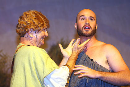 Peter Quince, played by Lynn D. Farris, and Nick Bottom, played by J.P. Allen, discuss the play they are producing. Nick Bottom gets the part of the main role of Pyramus. He wants to dominate others by suggesting himself for the characters of Thisbe, The Lion and Pyramus at the same time.