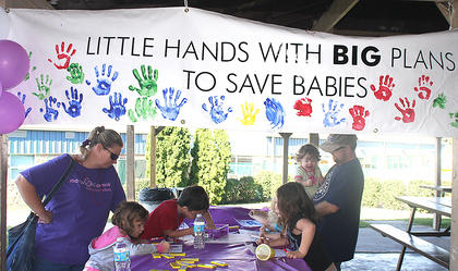 Children color underneath the pavilion at the park before the March for Babies walk begins.