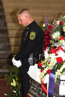Officer Aaron Caldwell stands watch next to the chief&#039;s casket.