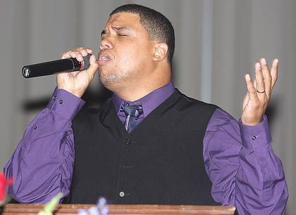 "Eric McElroy sings ""Say the Name of Jesus"" during the funeral service."
