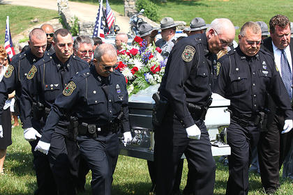 Members of the Lebanon Police Department carry Bell&#039;s casket to the gravesite.