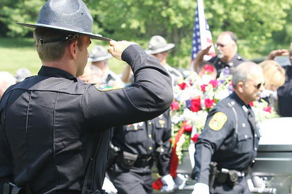 A law enforcement official salutes a casket carrying Lebanon Police Chief Joe Bell, who passed away June 6. He was laid to rest Saturday, June 11.